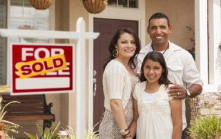 Happy family in front of their home with a sold sign in front.